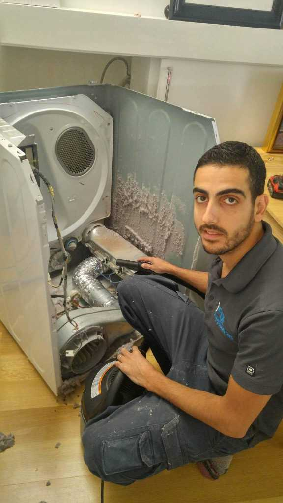 dryer disassembled by repair professional with lint inside