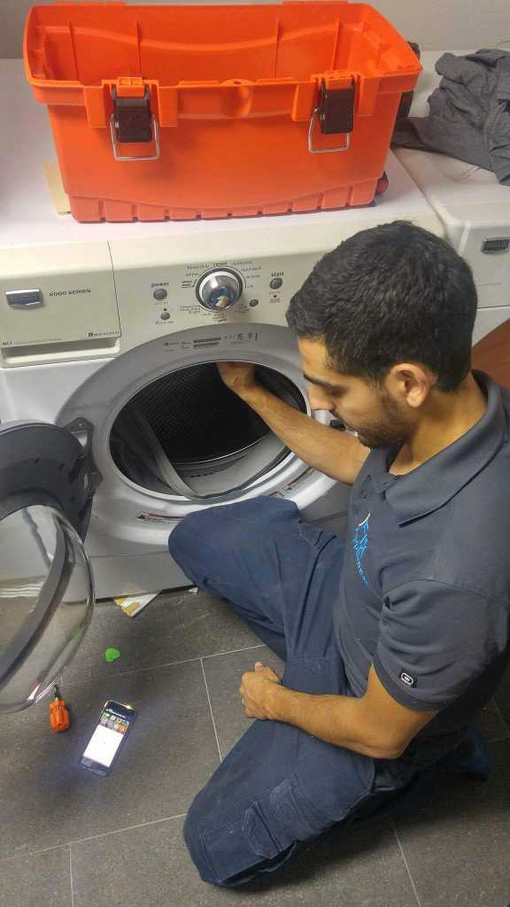 washing machine repair technician checking the washer