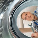 appliance repair technician looking inside the washer