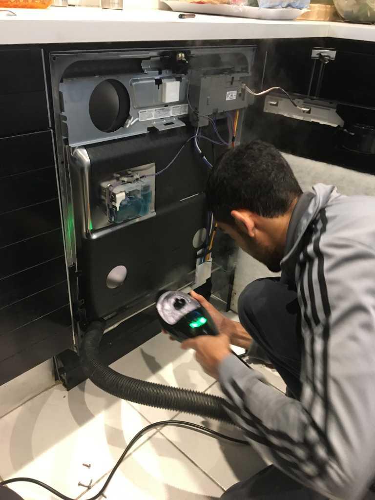 a technician fixing a dishwasher appliance