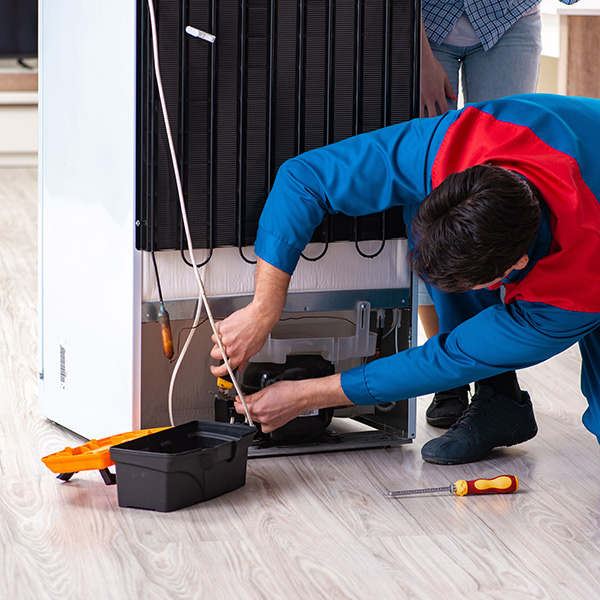 fridge repair technician fixing a refidgerator in Kitchener